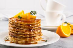 自创早餐或早午餐:美国风格的薄煎饼服务用桔子并且洒了糖浆 免版税库存图片