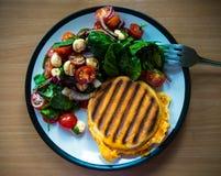 自创早餐烤了英国miffin三明治服务用旁边沙拉:西红柿、珍珠无盐干酪和菠菜 免版税库存照片
