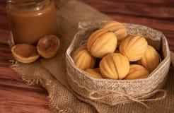自创曲奇饼塑造了有奶油煮沸的浓缩的milkt的坚果在木桌上 免版税图库摄影