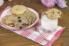 自创曲奇饼:椰子,燕麦粥,巧克力,在一张木桌上,与一杯牛奶,以一个夏天为背景 免版税图库摄影