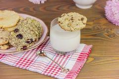 自创曲奇饼:椰子,燕麦粥,巧克力,在一张木桌上,与一杯牛奶,以一个夏天为背景 免版税库存照片