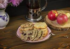 自创曲奇饼:椰子,燕麦粥,巧克力,在一张木桌上,与茶罐,在土气构成的背景与 图库摄影