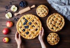 自创有机苹果饼面包店产品握在黑暗的木厨房用桌上的女性手与上升, bluberry 免版税库存图片