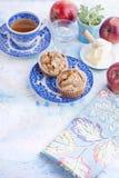 自创松饼用在一块蓝色板材的杏仁早餐和茶的在杯子 一杯水和红色新鲜的苹果和黄油 库存照片