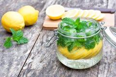 自创果汁饮料用柠檬薄荷和冰在桌上 免版税库存照片