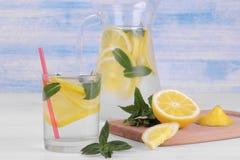 自创柠檬水用柠檬和薄菏在一个玻璃水罐和一块玻璃在柠檬旁边在白色和蓝色木背景 库存图片