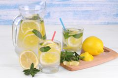 自创柠檬水用柠檬和薄菏在一个玻璃水罐和一块玻璃在柠檬旁边在白色和蓝色木背景 免版税库存图片