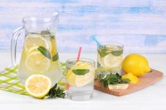 自创柠檬水用柠檬和薄菏在一个玻璃水罐和一块玻璃在柠檬旁边在白色和蓝色木背景 库存照片