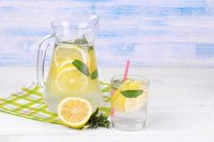 自创柠檬水用柠檬和薄菏在一个玻璃水罐和一块玻璃在柠檬旁边在白色和蓝色木背景 免版税库存照片