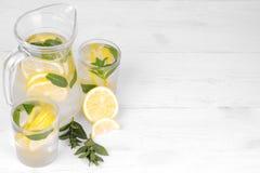 自创柠檬水用柠檬和薄菏在一个玻璃水罐和一块玻璃在柠檬旁边在白色木背景 库存照片