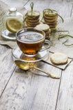 自创柠檬糖屑曲奇饼和杯子在木桌上的热的茶 免版税库存图片