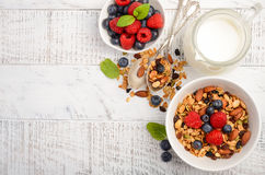 自创格兰诺拉麦片用在白色木背景的新鲜的莓果 免版税库存照片