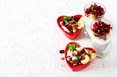 自创格兰诺拉麦片用在红色心脏板材的酸奶在白色桌上 浪漫您的文本的早餐自由空间 免版税库存照片