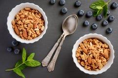 自创格兰诺拉麦片用在黑背景的蓝莓 免版税库存图片
