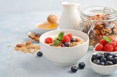 自创格兰诺拉麦片用酸奶和新鲜的莓果,健康早餐概念 免版税库存图片