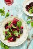 自创桃红色馄饨意大利式饺子用山羊乳干酪装饰了甜菜叶子、甜菜根切片和蔓越桔 免版税库存图片