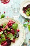 自创桃红色馄饨意大利式饺子用山羊乳干酪装饰了甜菜叶子、甜菜根切片和蔓越桔 免版税图库摄影