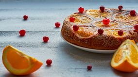 自创橙色蛋糕用新鲜的红色蔓越桔和橙色切片在灰色背景 柑橘饼 赠送阅本空间 平的位置 免版税库存图片