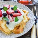 自创比利时华夫饼干用酸奶、草莓和蓝莓,早餐时间,正方形 库存照片