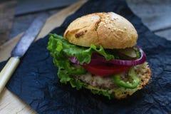 自创汉堡用新鲜的蕃茄、莴苣、葱和油煎的土豆在土气木板 快餐,不健康吃 库存图片