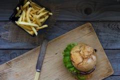 自创汉堡用新鲜的蕃茄、莴苣、葱和油煎的土豆在土气木板 快餐,不健康吃 免版税库存图片