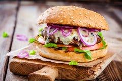 自创汉堡用牛肉炸肉排、苹果、莴苣、葱和青纹干酪 免版税库存图片