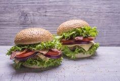 自创汉堡用牛肉炸肉排,新鲜蔬菜沙拉,蕃茄,葱,乳酪,番茄酱,与芝麻籽的小圆面包在灰色 免版税库存照片