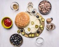 自创汉堡的,金枪鱼,小圆面包,调味汁,橄榄,在木土气背景顶视图边界,地方文本的香料成份 免版税库存图片