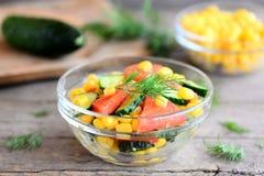 自创沙拉用新鲜的蕃茄、黄瓜和罐装玉米穿戴了与橄榄油和柠檬汁 在碗的素食者沙拉 图库摄影
