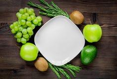 自创沙拉的有机食品与在木书桌背景顶视图大模型的绿色菜 免版税库存照片