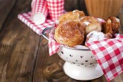 自创油煎的球用搽粉的糖 在红色笼子和玻璃的餐巾 背景棕色木 传统烘烤的荷兰 免版税库存图片