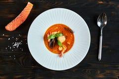 自创海鲜汤用西红柿酱和椰奶在一个老木盘子 免版税库存图片