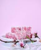 自创澳大利亚样式桃红色心脏形状小lamington结块与春天开花-与copyspace的垂直 免版税库存图片