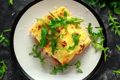 自创烤宽面条用剁碎的牛肉博洛涅塞和调味酱调味冠上了野生芝麻菜,帕尔马干酪 库存图片