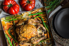 自创烤被充塞的鸡用菜红萝卜,白薯,芦笋,葱,迷迭香 免版税库存照片