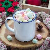 自创热巧克力冠上了用在搪瓷杯子,在木日志,在背景,正方形的温暖的围巾的逗留的蛋白软糖 免版税库存照片