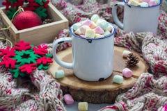自创热巧克力冠上了用在搪瓷杯子,在背景的温暖的围巾的蛋白软糖 库存图片