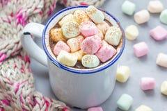 自创热巧克力冠上了用在搪瓷杯子,在背景的温暖的围巾的蛋白软糖 免版税库存照片