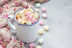 自创热巧克力冠上了用在搪瓷杯子,在背景,拷贝空间的温暖的围巾的蛋白软糖 免版税图库摄影
