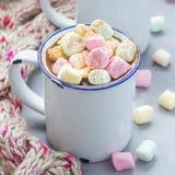 自创热巧克力冠上了用在搪瓷杯子,在背景,正方形的温暖的围巾的蛋白软糖 库存图片