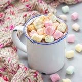 自创热巧克力冠上了用在搪瓷杯子,在背景,正方形的温暖的围巾的蛋白软糖 库存照片
