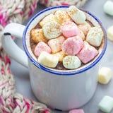 自创热巧克力冠上了用在搪瓷杯子,在背景,正方形的温暖的围巾的蛋白软糖 免版税图库摄影