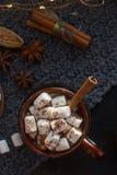 自创热巧克力用蛋白软糖、桂香和香料在黑暗的背景,顶视图 可口圣诞节或新年饮料 免版税库存图片