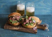 自创牛排牛肉汉堡和两玻璃啤酒 免版税库存图片