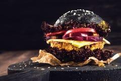 自创的汉堡包 素食者黑鸡豆用一道炸肉排、蕃茄、乳酪、黑暗的莴苣和紫洋葱在土气木桌上 T 库存图片