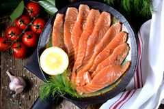自创盐味的三文鱼用莳萝和西红柿在老木背景 库存照片