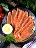 自创盐味的三文鱼用莳萝和西红柿在老木背景 库存图片