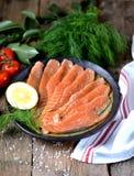 自创盐味的三文鱼用莳萝和西红柿在老木背景 免版税库存照片