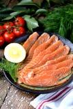 自创盐味的三文鱼用莳萝和西红柿在老木背景 图库摄影