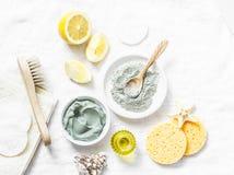自创秀丽脸面护理面具 黏土,柠檬,油,面部刷子-在轻的背景的美容品成份 免版税库存照片
